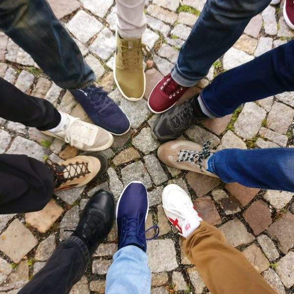 Circle of different feet and shoes to represent UDL philosophy that one size does not fit all.